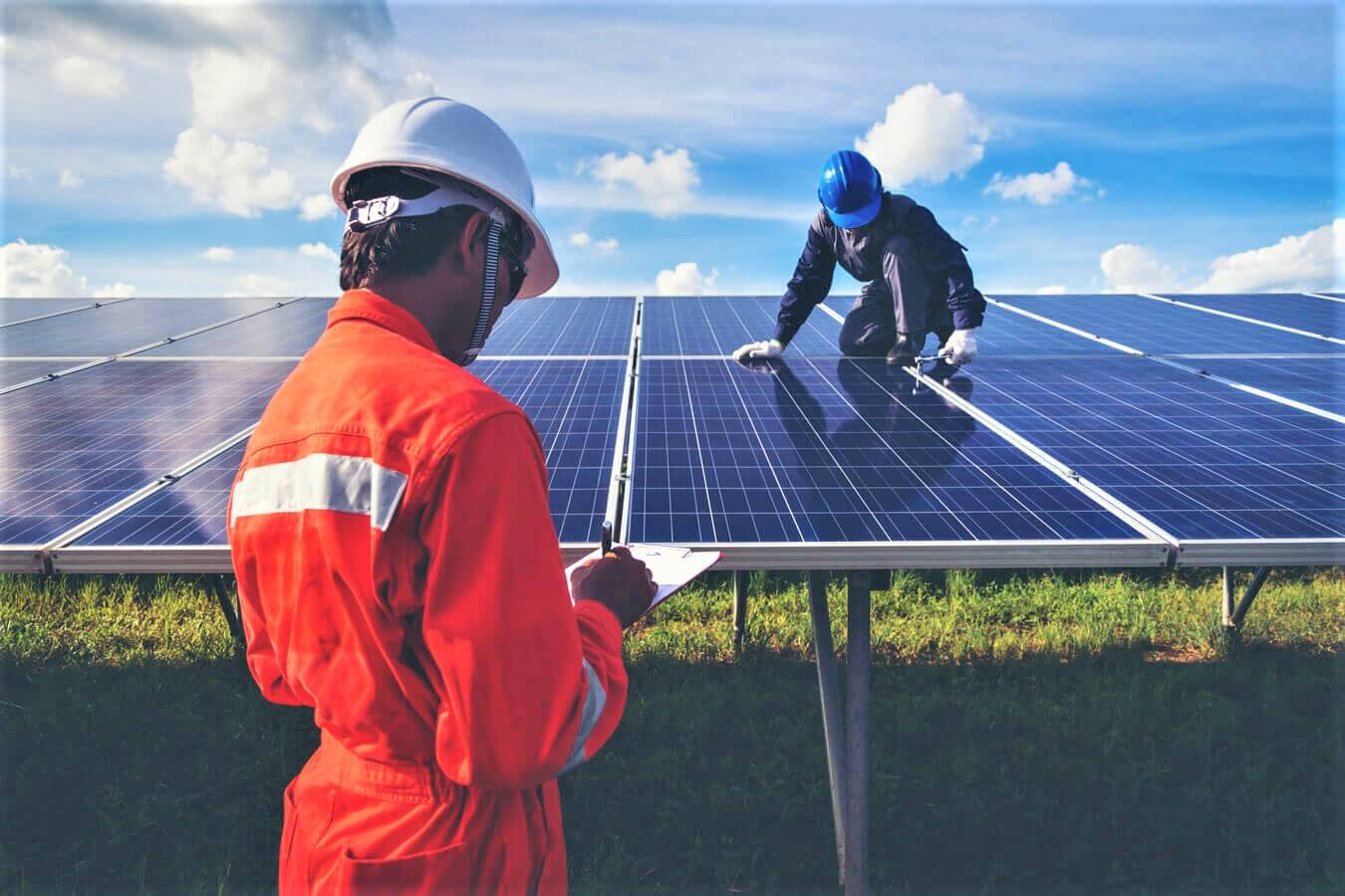 Two workers are installing a solar panel in the middle of the green fields. One of them is placing the panel while the other is an inspector who is controlling the correct installation. As Nexua Excellence Quality explains in this article, renewable energies will be the future of the power supply.